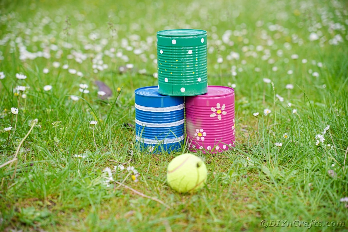 Blue pink and green tin cans on grass