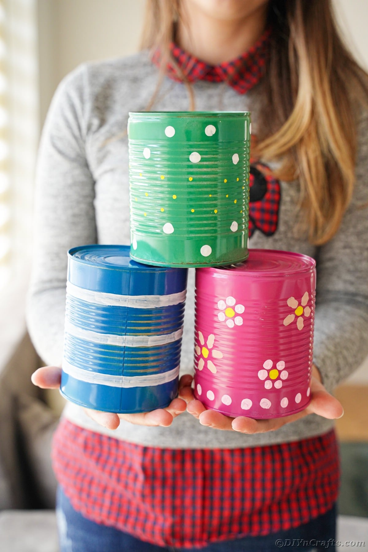 Woman holding pink green and blue tin cans