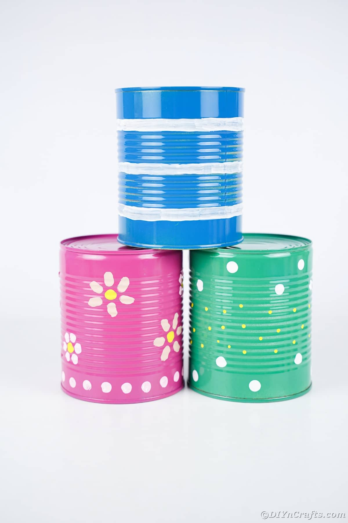 Stack of colorful tin cans on white table