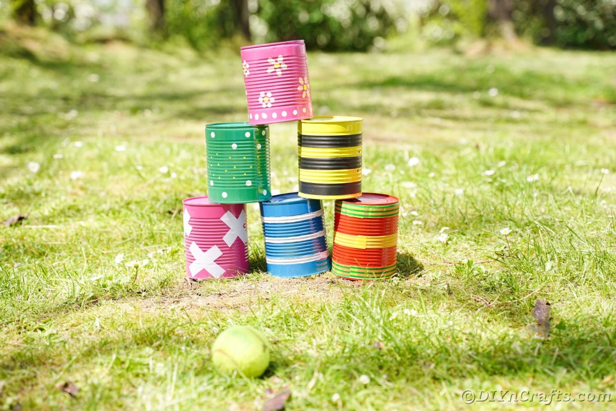 Six tin cans with colorful looks on grass