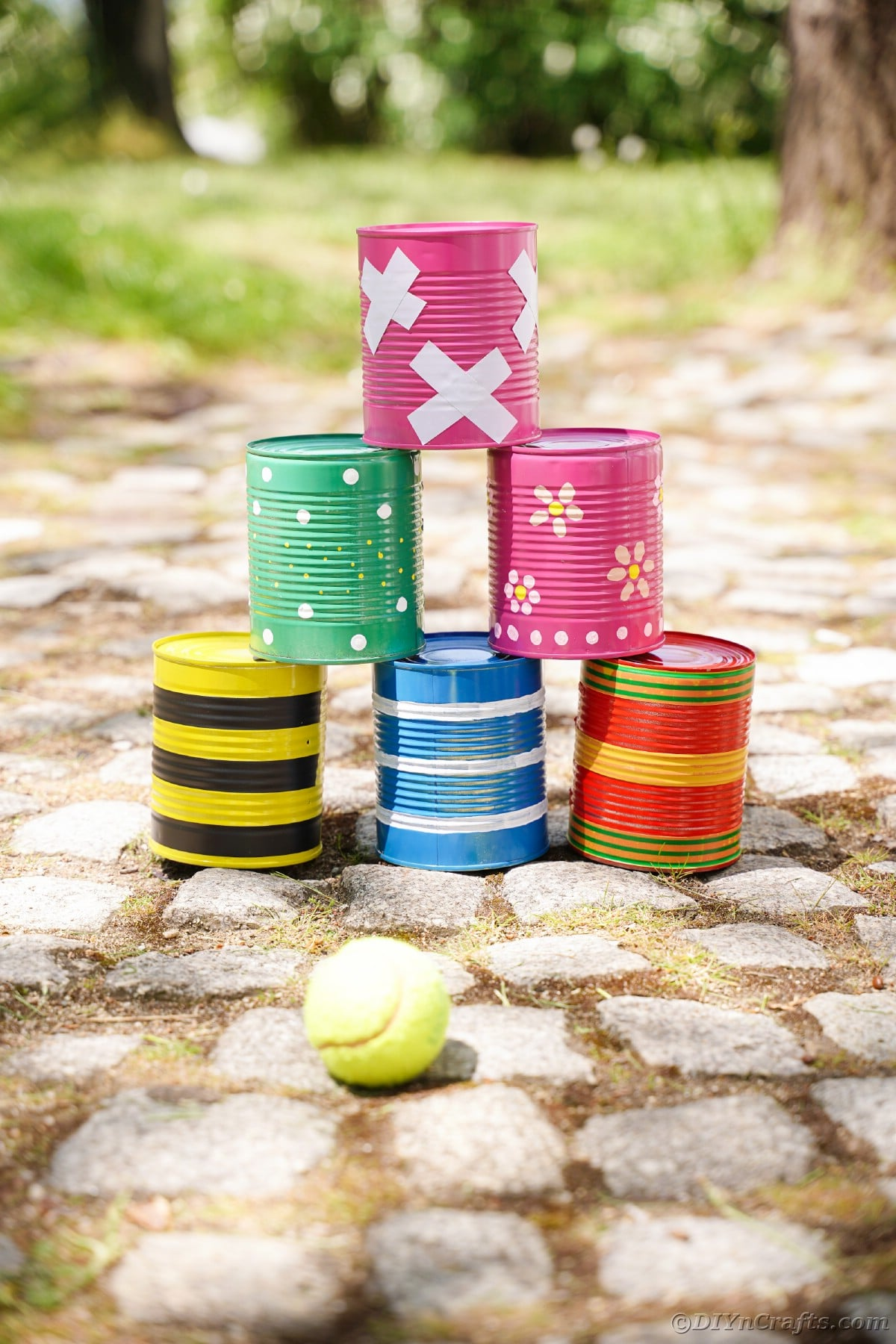 Stacked tin cans on cobblestone