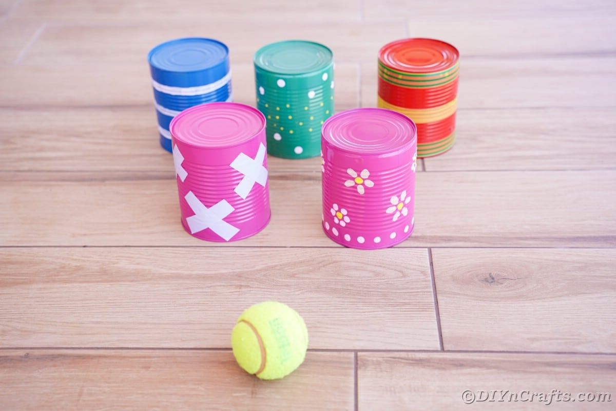 Painted cans on wood flooring with tennis ball