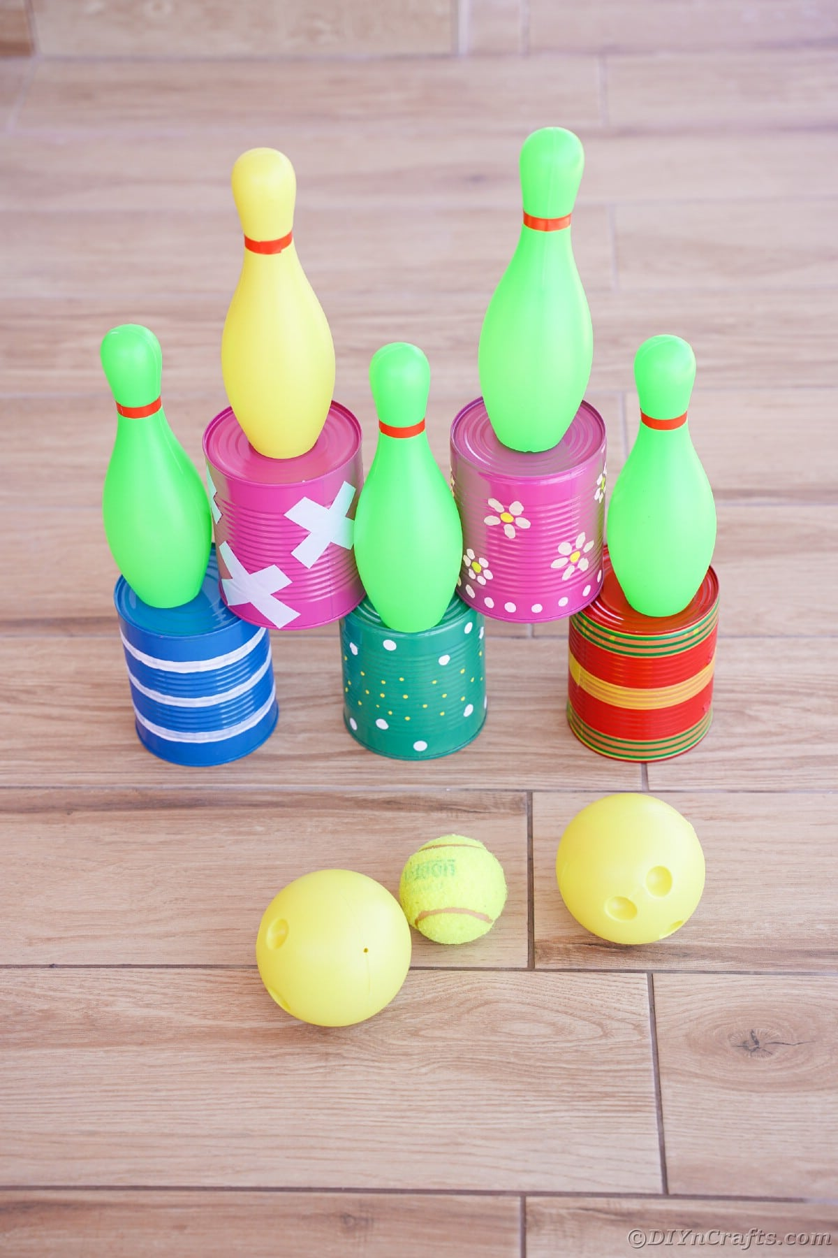 Tin cans with mini bowling pins on top and balls in front