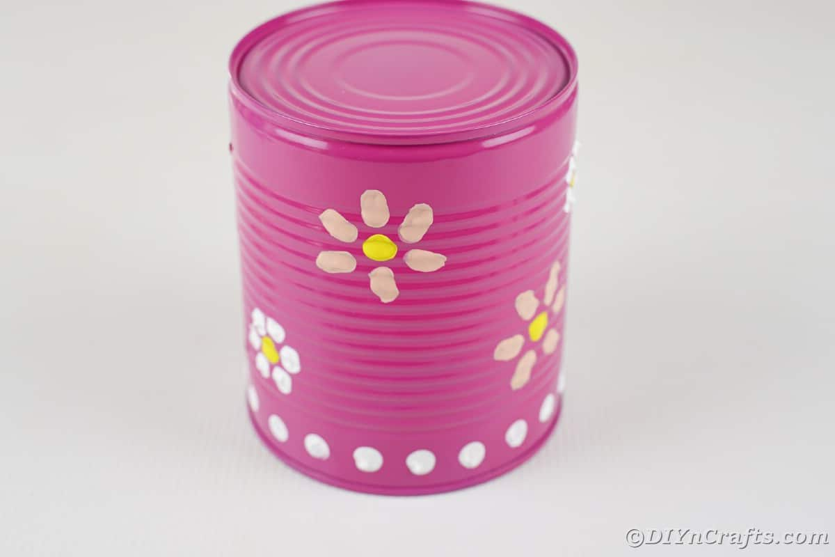 Pink can with white dots and pink flowers painted on the outside