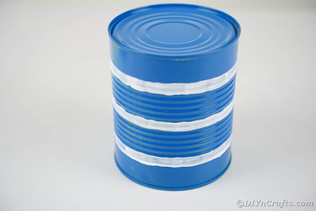 Blue tin can with white stripes painted around it