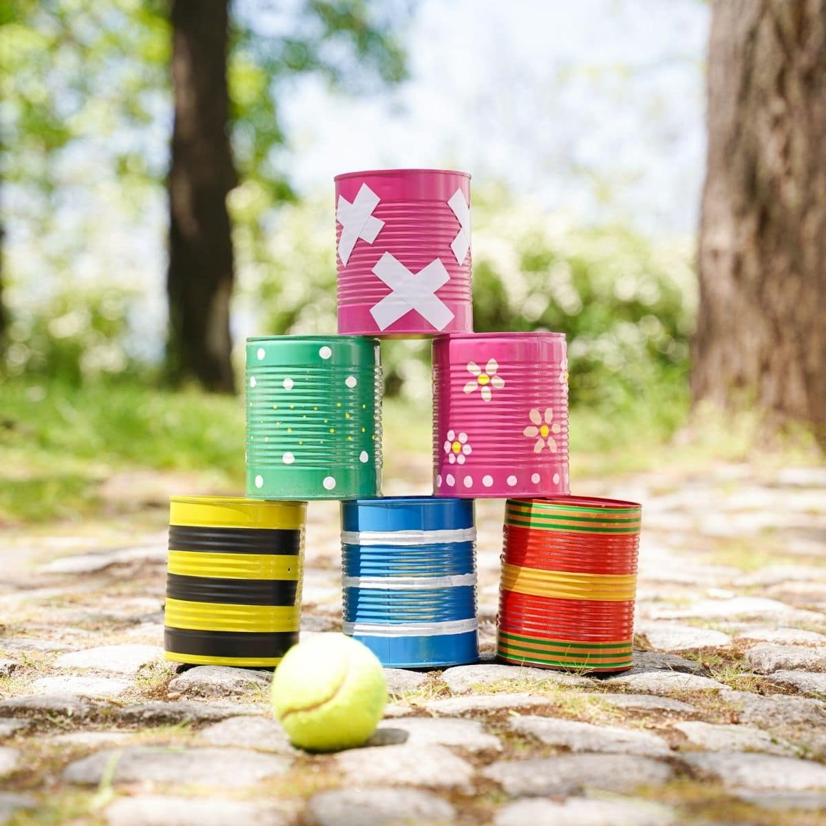 Six painted tin cans stacked together on stone