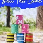 Stack of tin cans on cobblestone with blue banner that says upcycled tin can ball toss game
