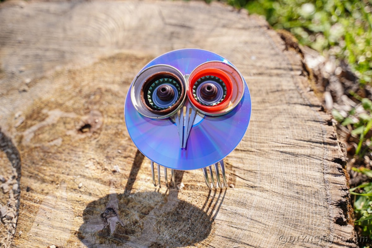 Wooden stump with DIY owl made from CDs on top