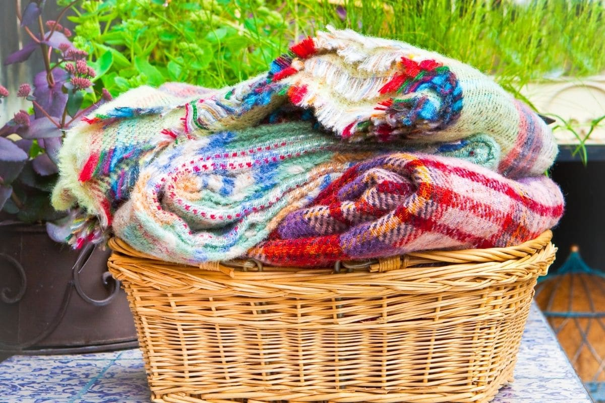 folded colorful blanket in a rattan basket