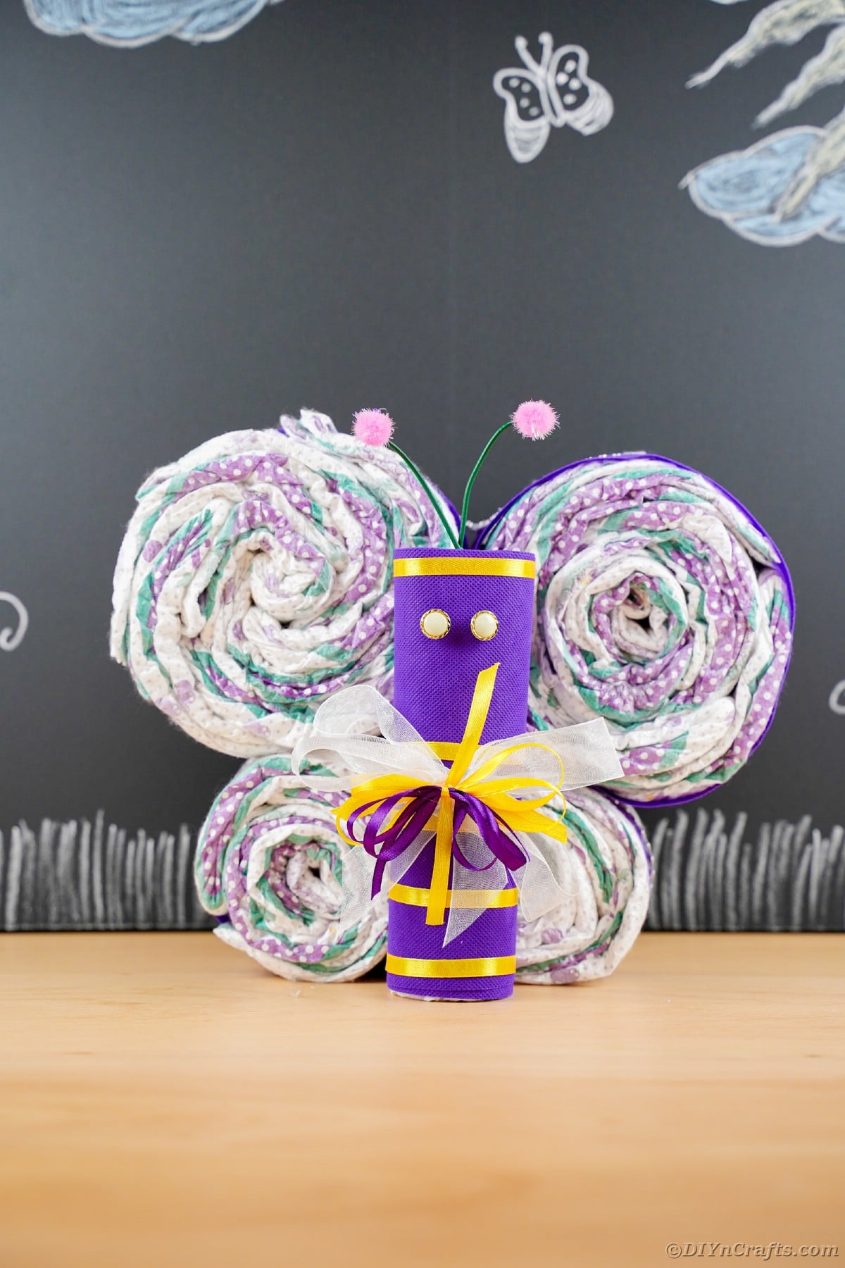 Purple diapers made into a butterfly in front of chalkboard
