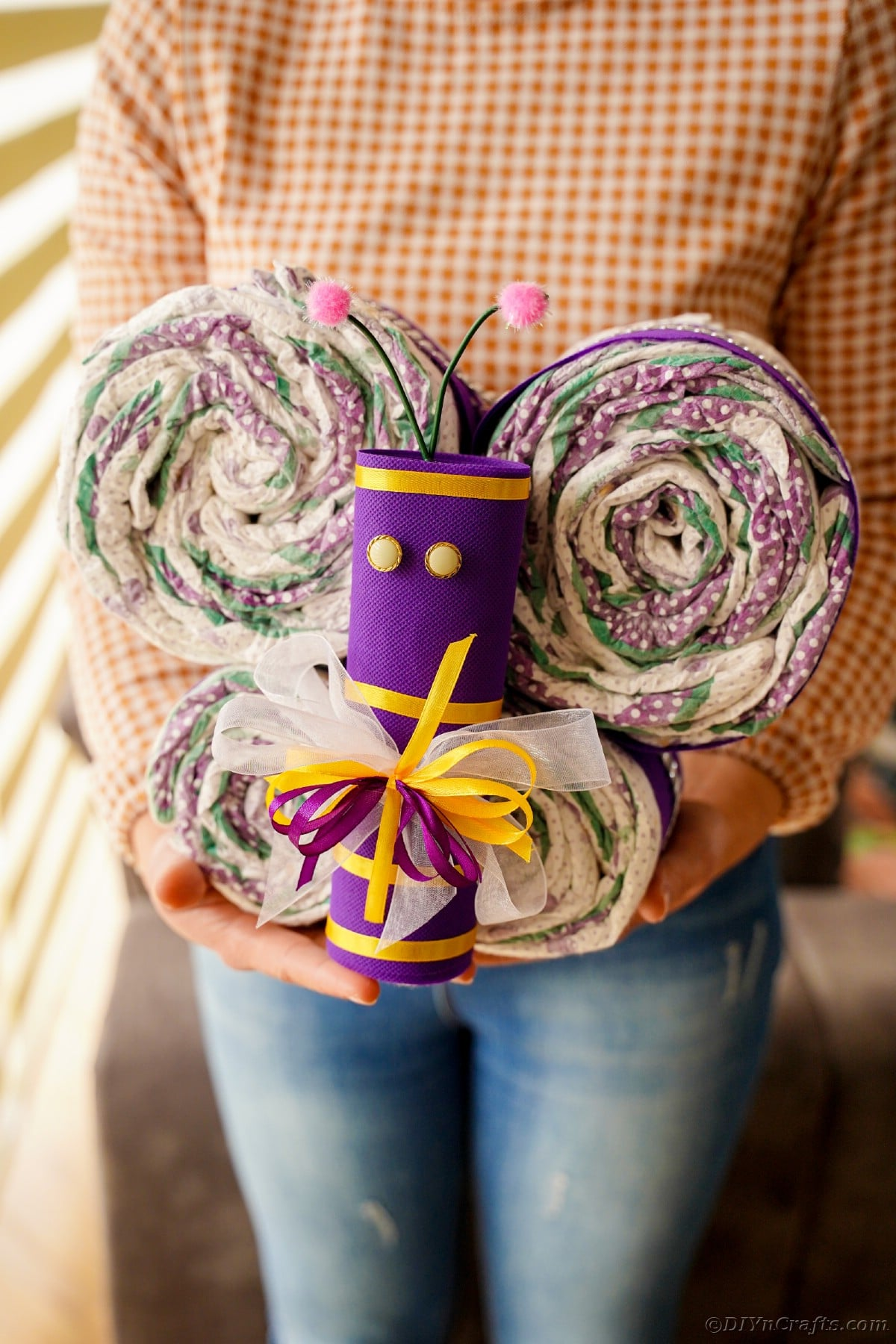 Woman in jeans holding diaper cake butterfly