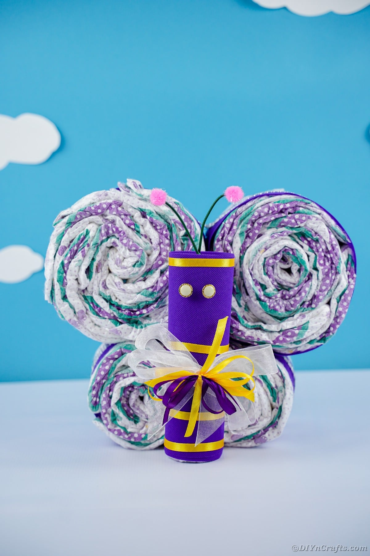 Diaper butterfly in purple and yellow in front of blue wall with clouds
