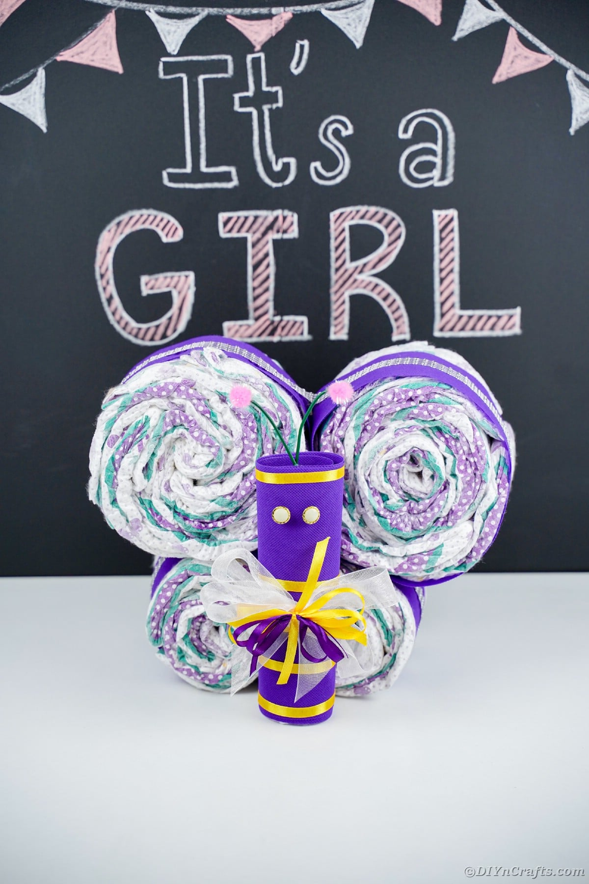 Purple butterfly made of diapers in front of its a girl chalkboard message