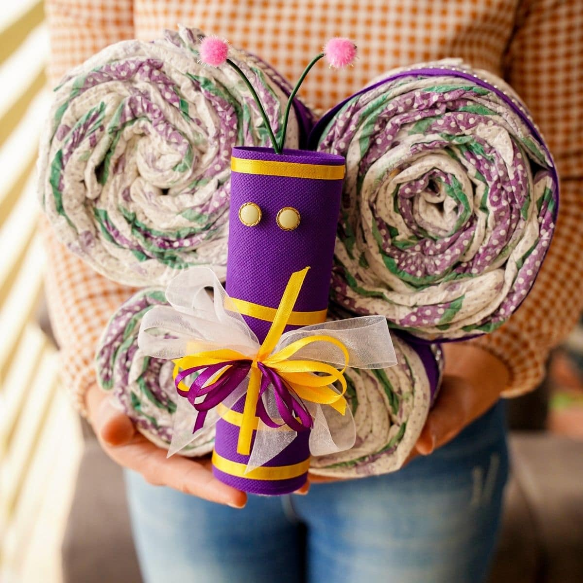 Woman in sweater holding butterfly diaper cake