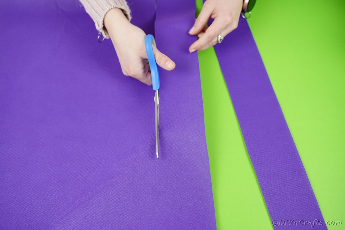 Cutting strips of purple paper