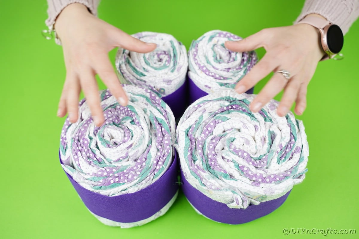 Four rolls of diapers wrapped in purple next to each other