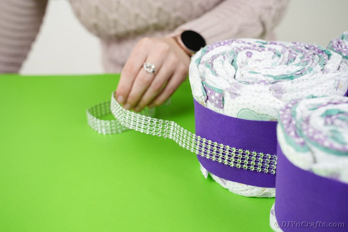Gluing beaded ribbon around the outside of the butterfly diaper cake body