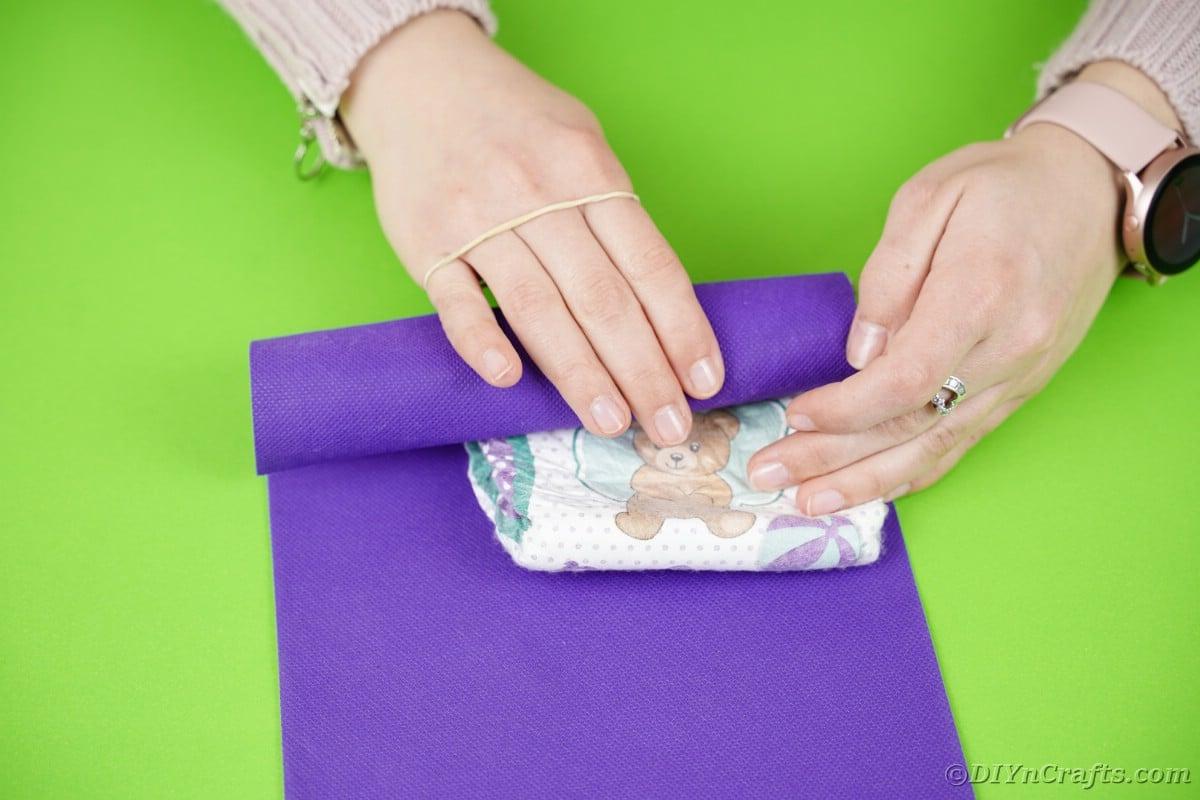 Rolling a diaper into purple paper