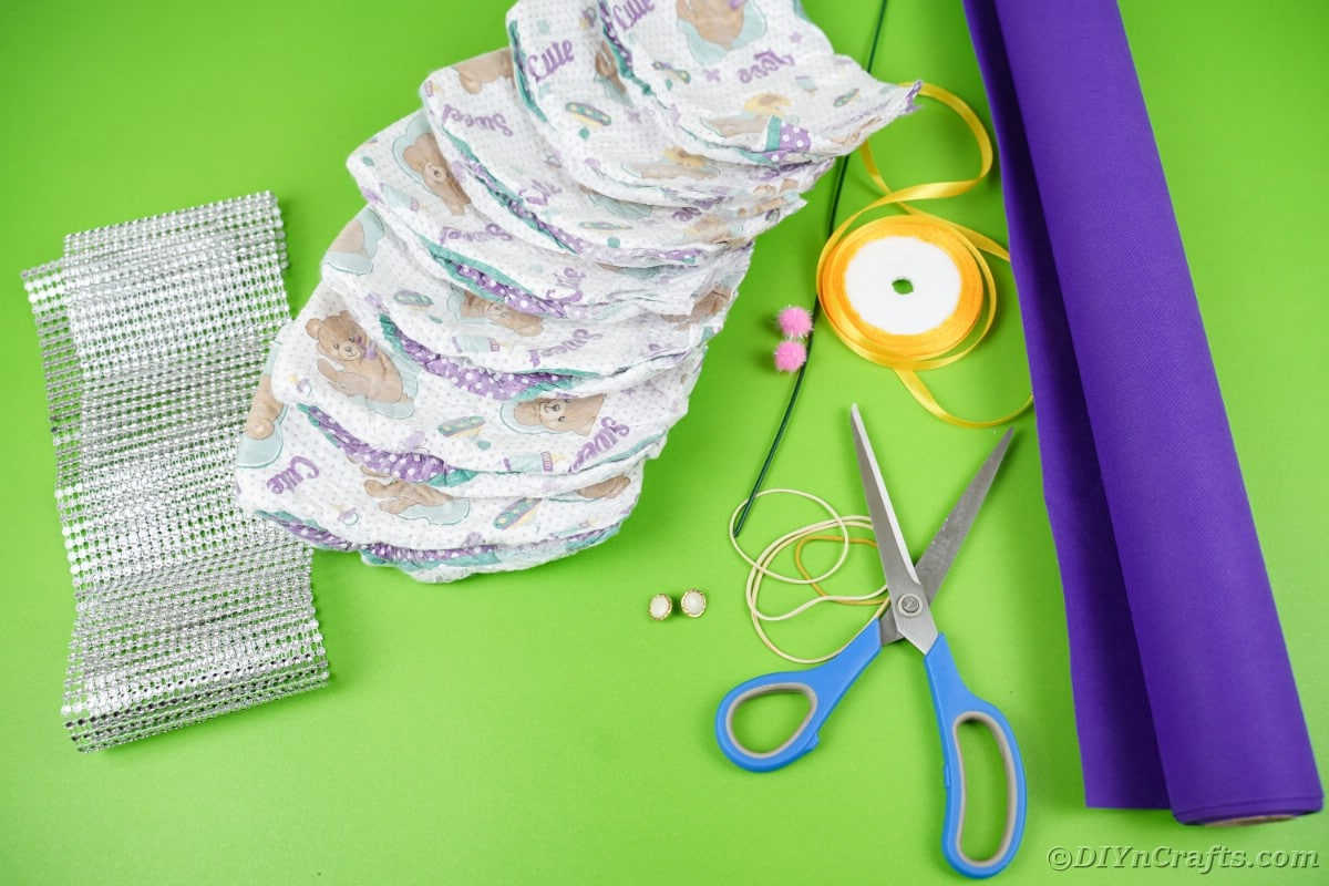 Diapers purple paper scissors and ribbon on green table