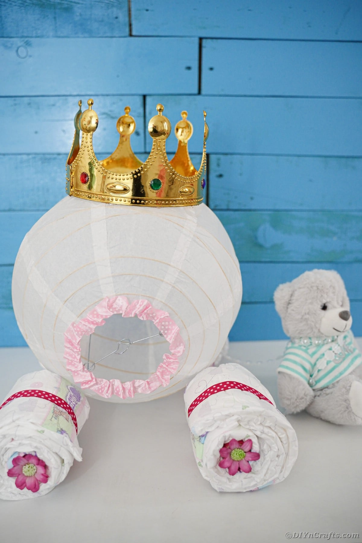 Diaper cake on white table by bear in front of blue wood background