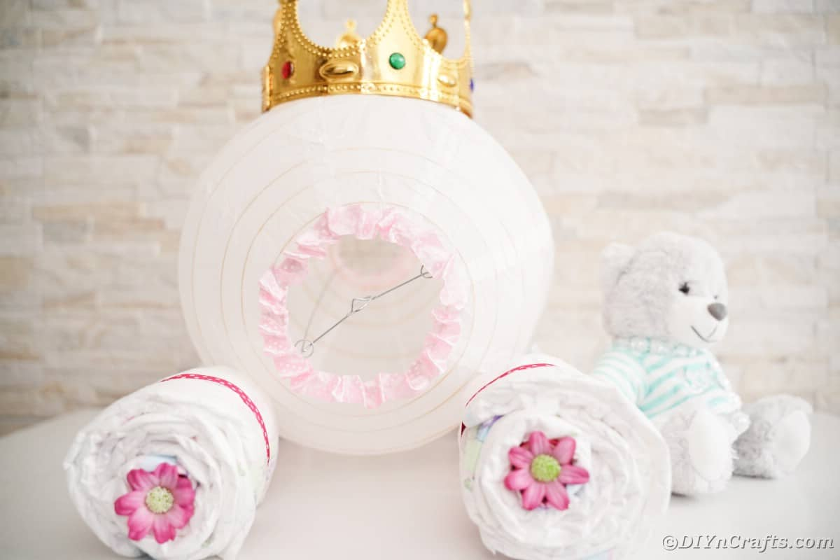 Cinderella carriage diaper cake on white table by white brick wall