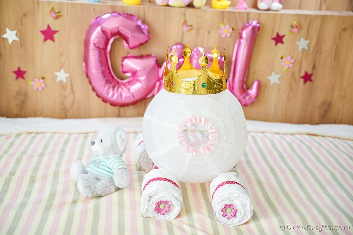 Diaper cake on bed in front of pink girl balloons