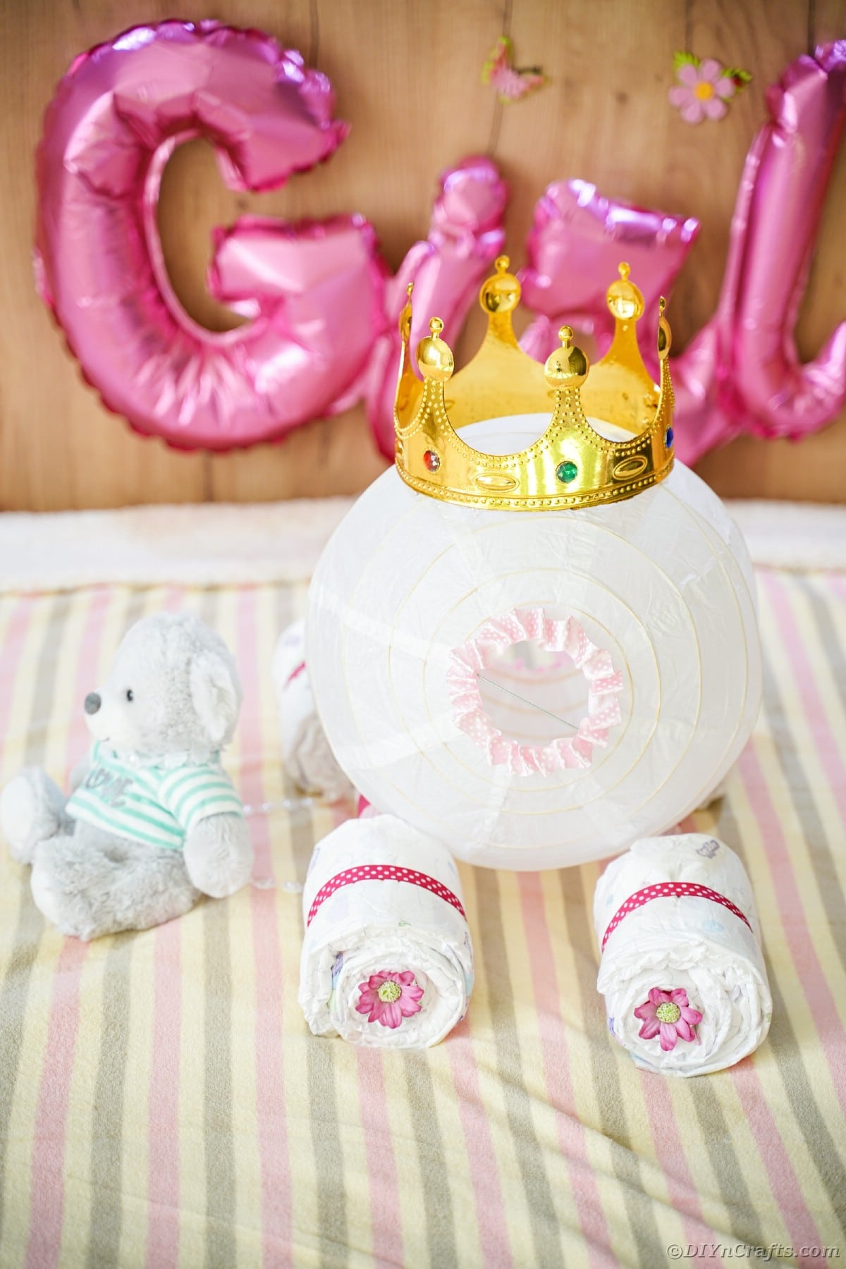 Carriage diaper cake on striped bedding with girl balloon in background