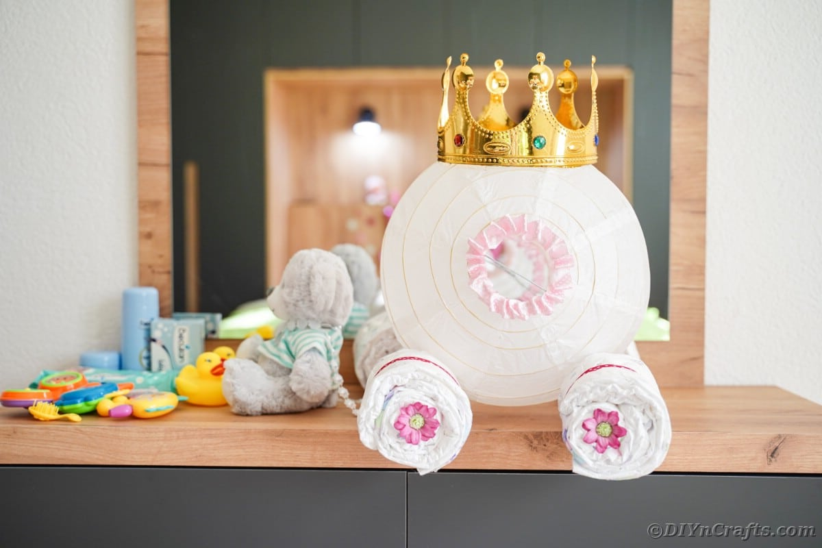 Cinderella carriage made out of lantern on dresser by teddy bear
