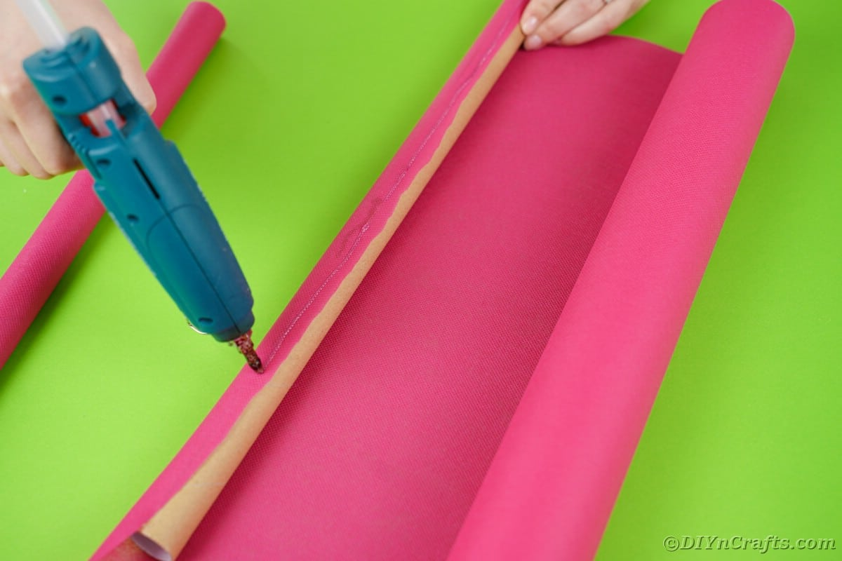 Gluing pink paper onto cardboard tube