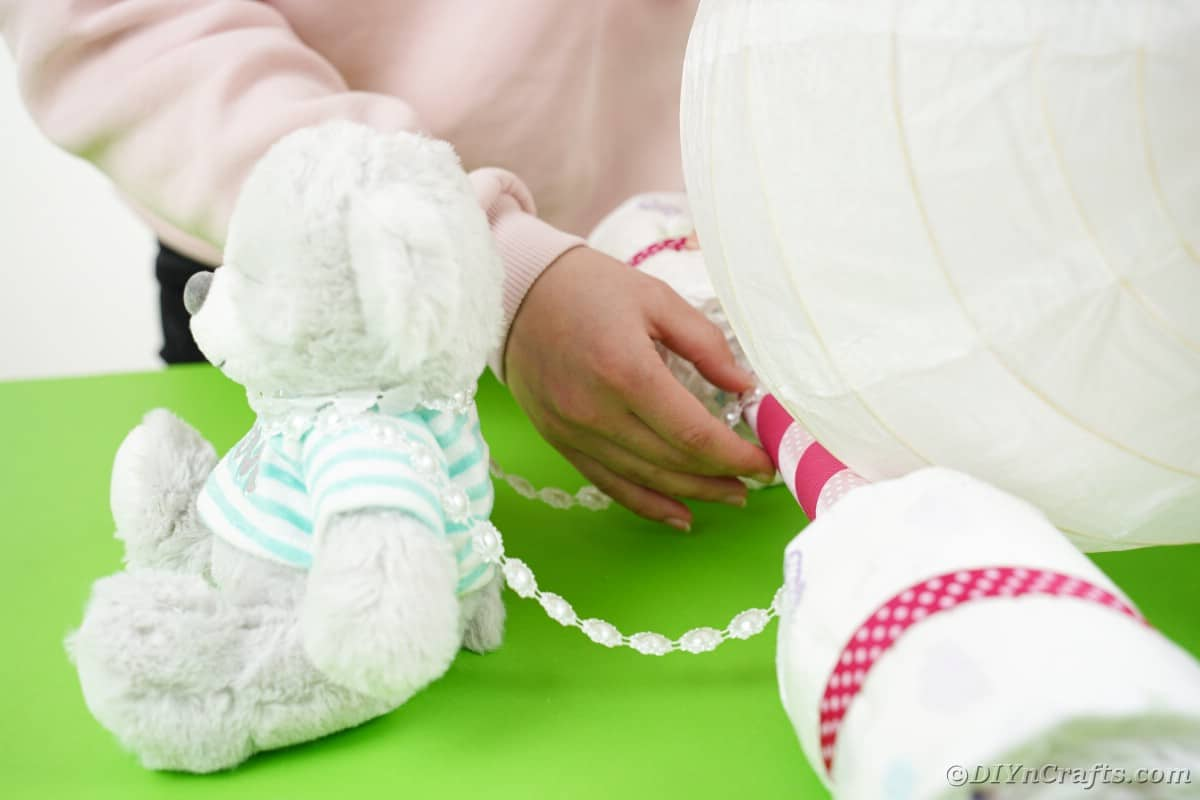 Woman attaching beads to diaper cake and bear