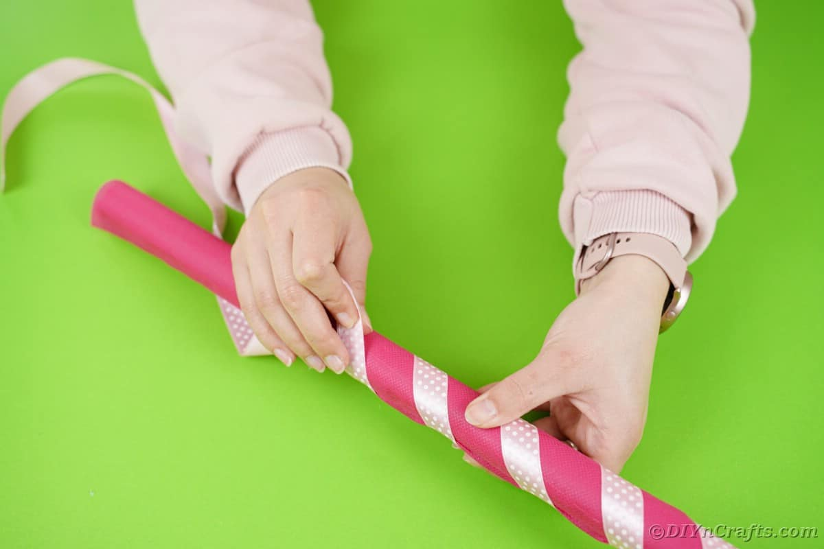 Wrapping pink ribbon around pink tissue roll