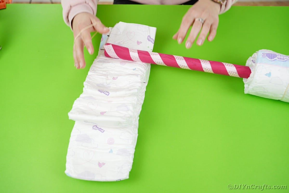 Diapers stacked on each other with white and pink stick laying on top