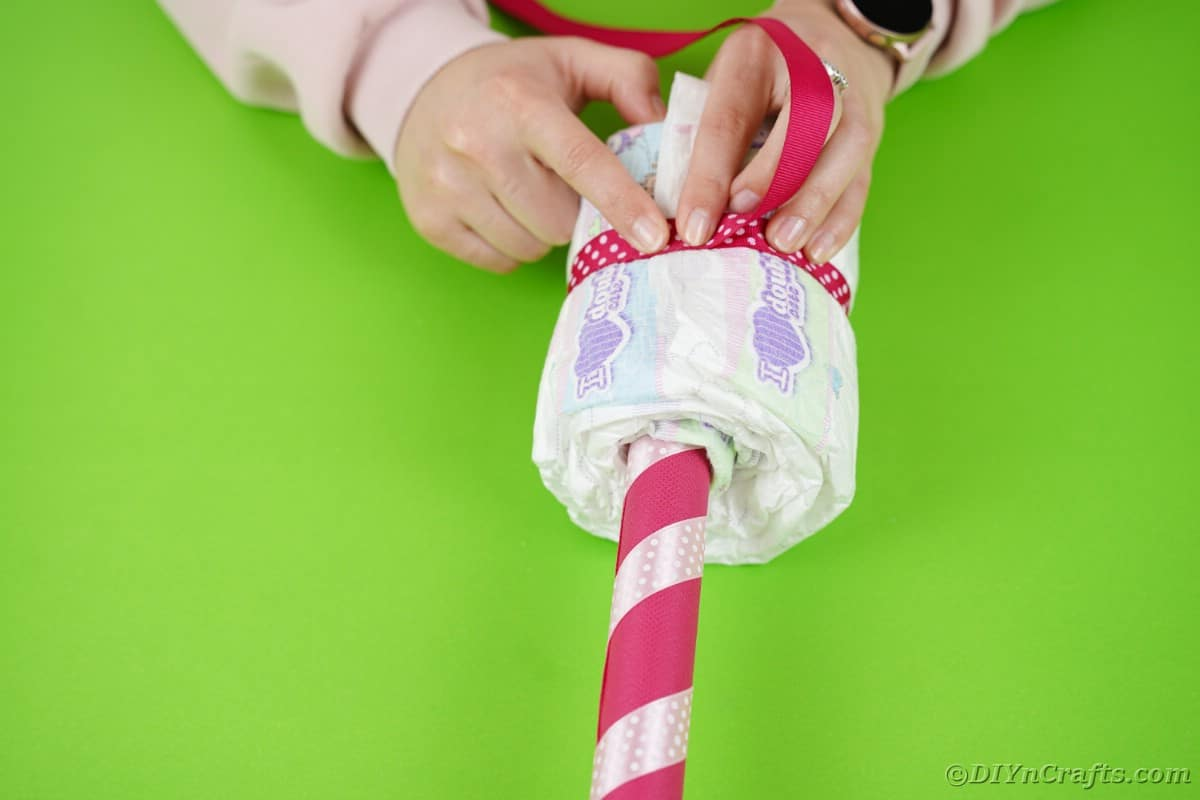 Gluing ribbon onto diaper rolled over pink stick