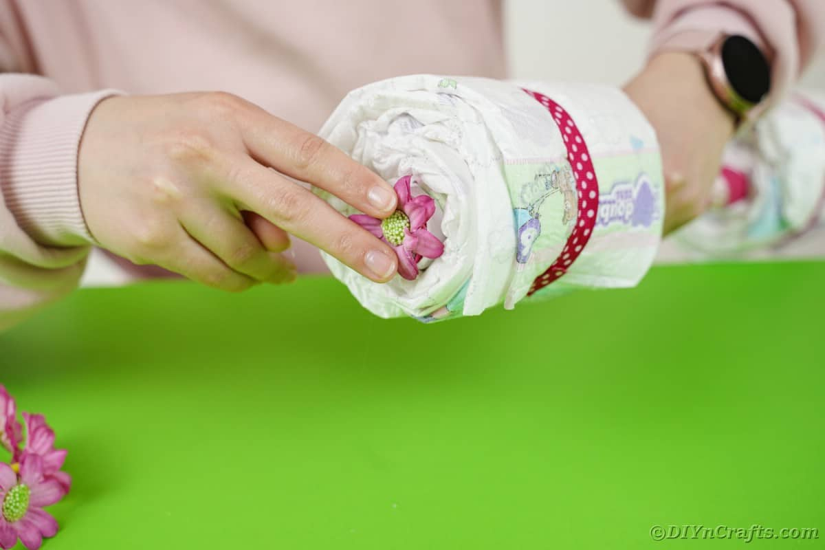 Adding pink flower to end of rolled diaper