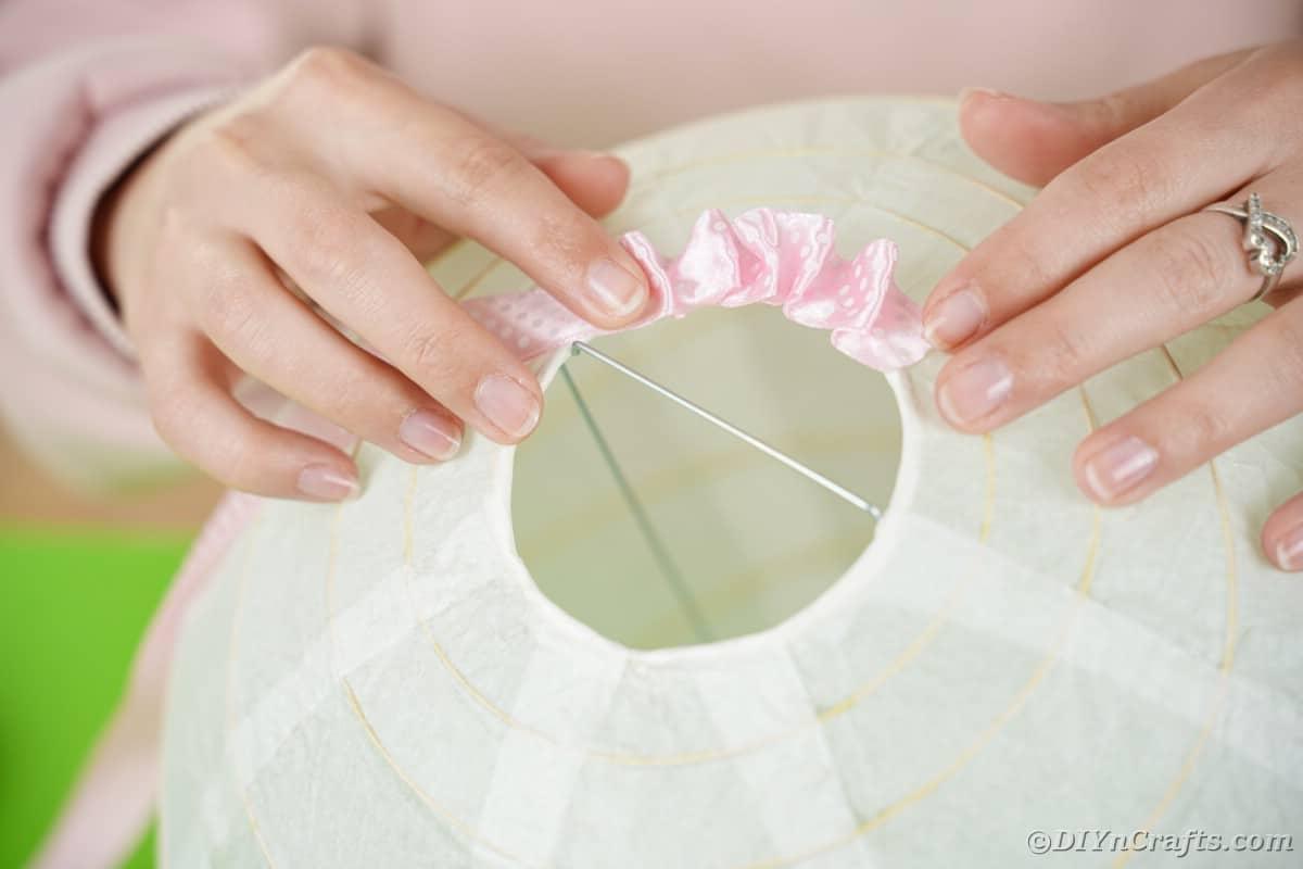 Gluing ribbon on paper lantern opening