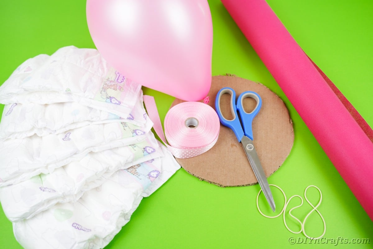 Diapers balloons scissors and ribbon on green table