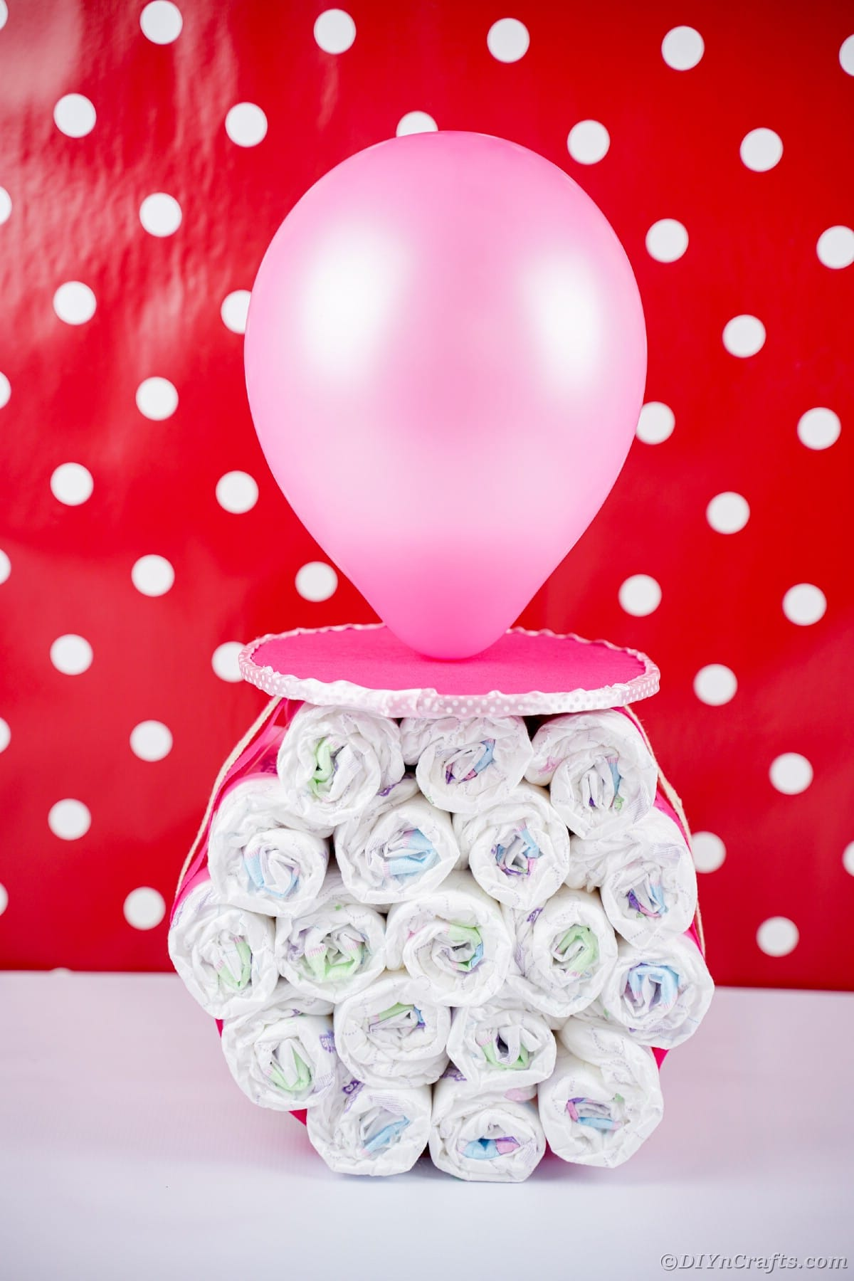 Standing diaper cake pacifier in front of red and white wall