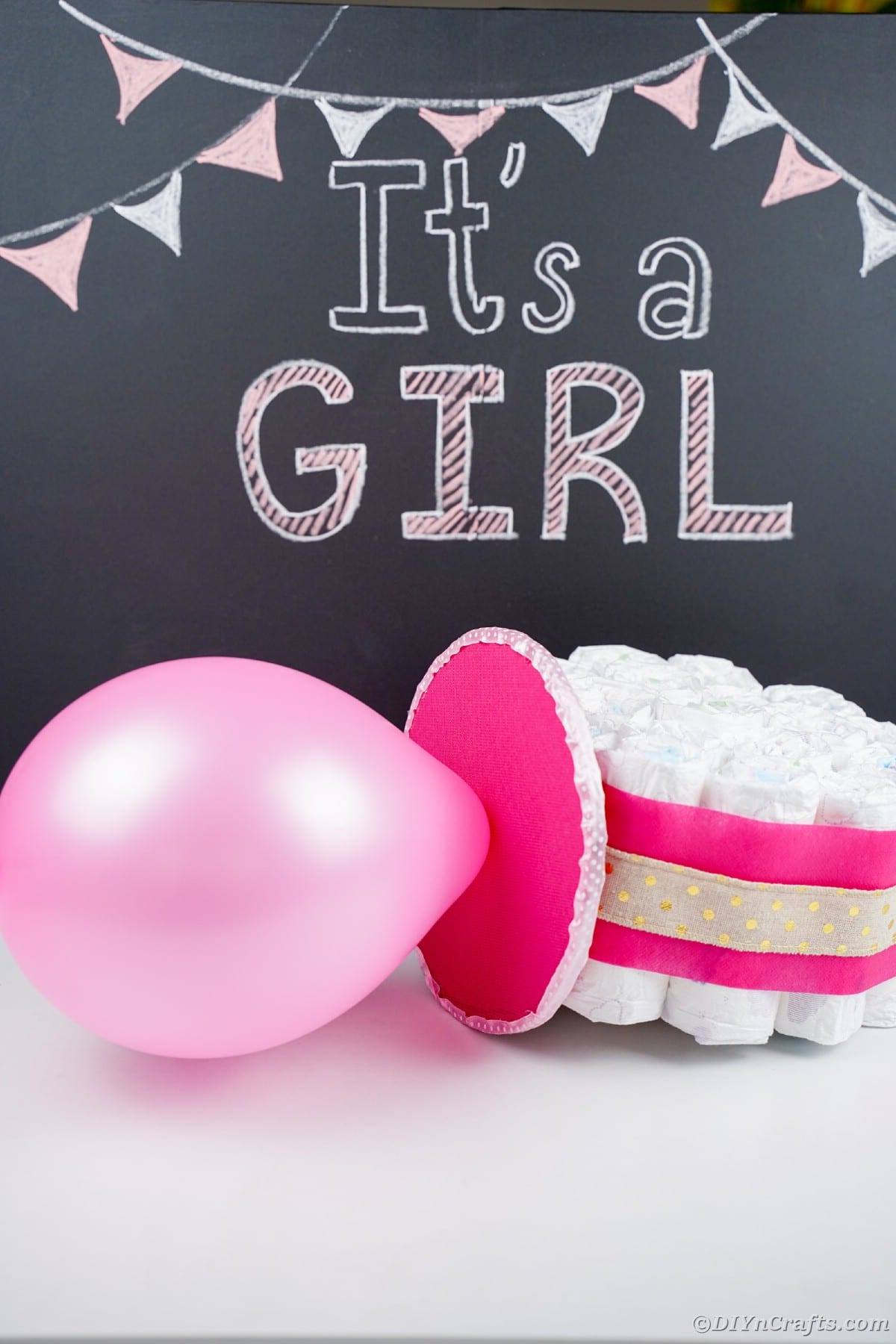 Pink balloon and diaper pacifier on table