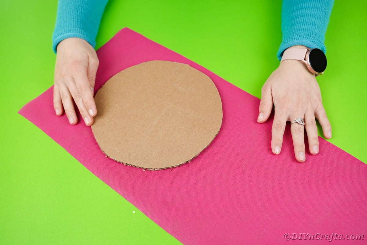 Cardboard circle in middle of large piece of pink paper