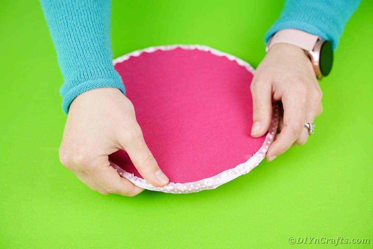 Handing putting ribbon on top edge of pink circle