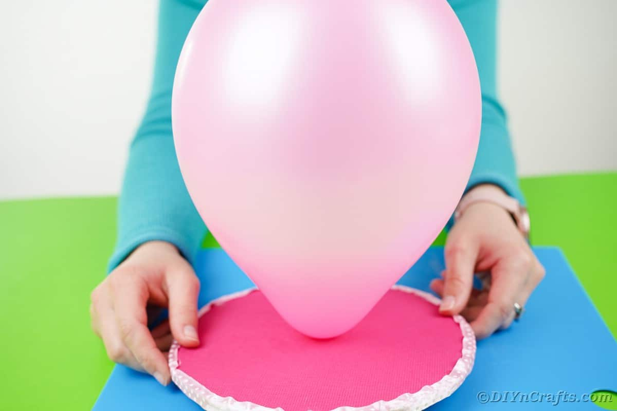 Pushing balloon through hole in pink cardboard circle