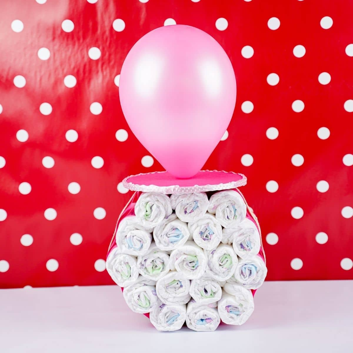 Pacifier diaper cake standing up in front of red polka dot wall