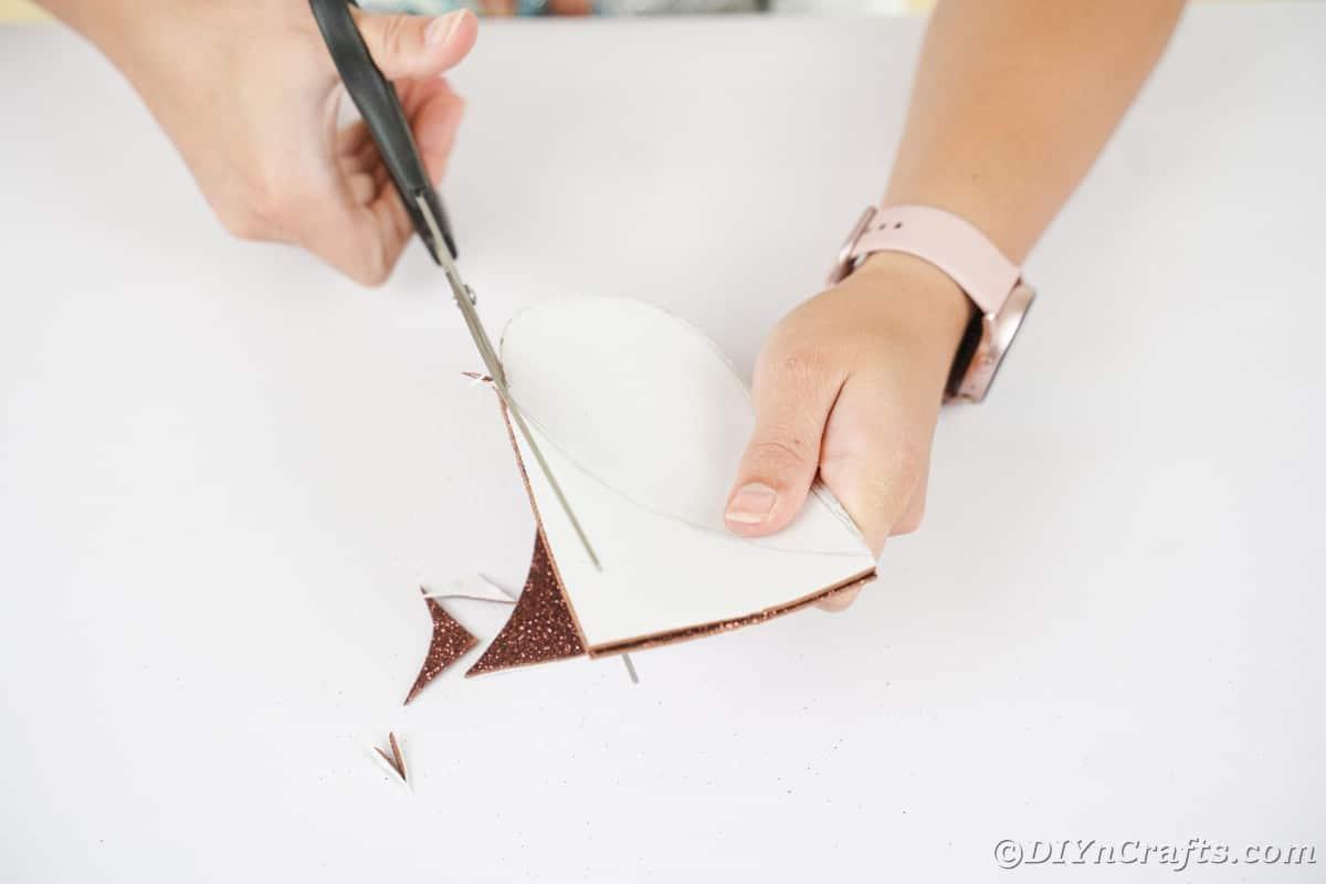 Mão segurando uma tesoura preta cortando papel de espuma