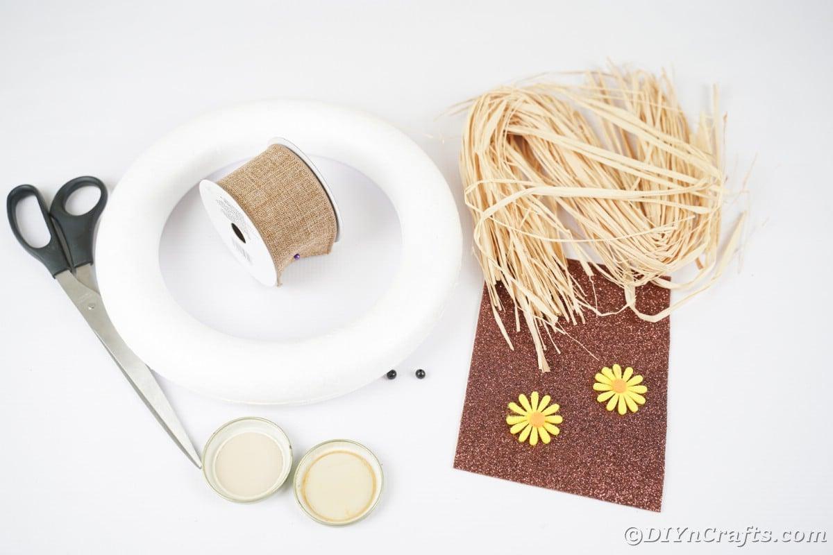 Grinalda de espuma forma de papel de ráfia e fita na mesa branca