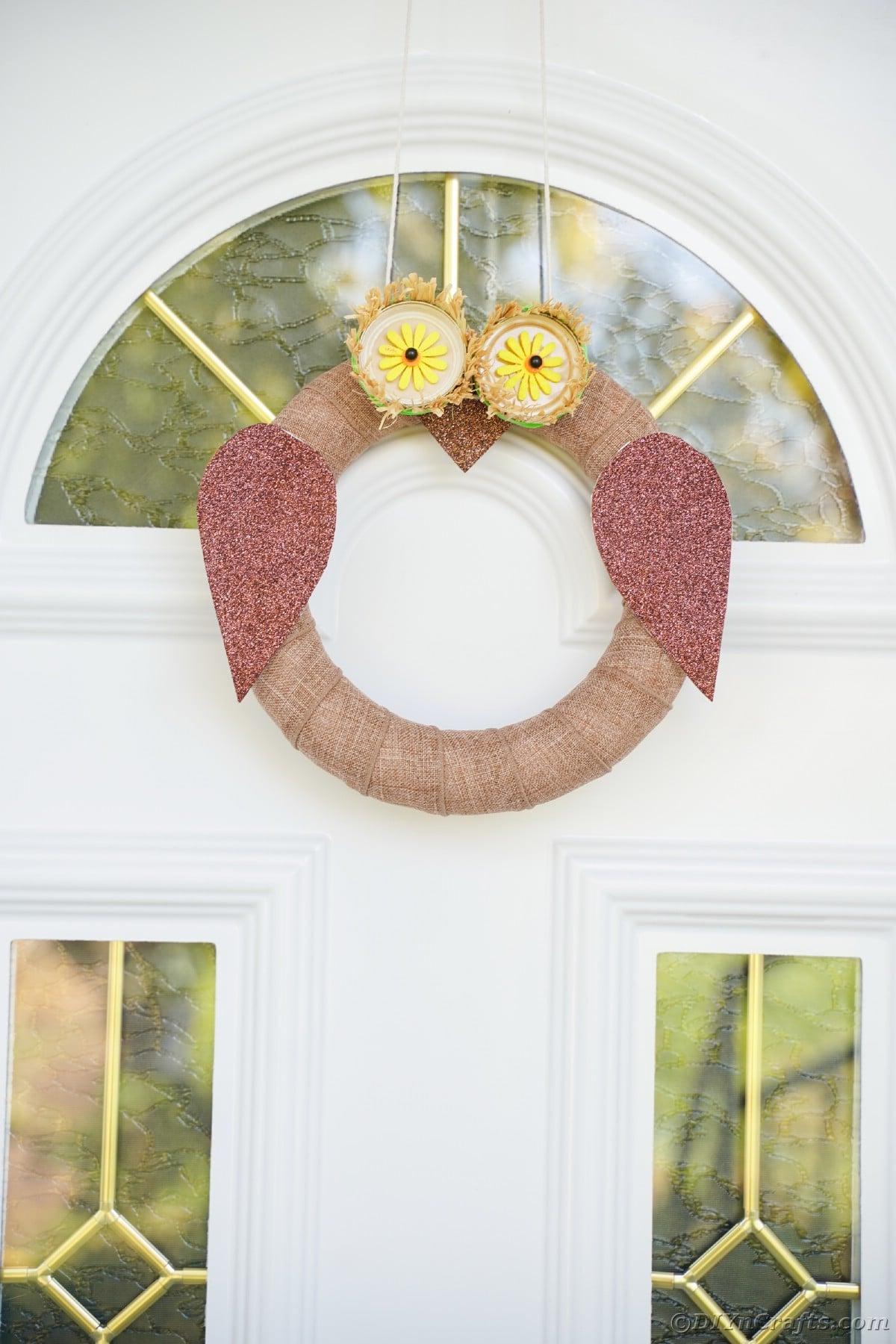 Guirlanda de coruja pendurada na porta branca da frente com painéis de vidro