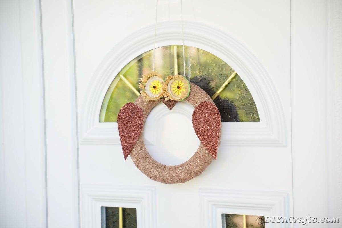 Grinalda de serapilheira parece uma coruja na porta branca
