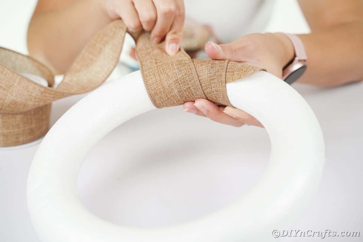 Mão envolvendo uma fita de serapilheira em torno da forma de coroa de espuma branca