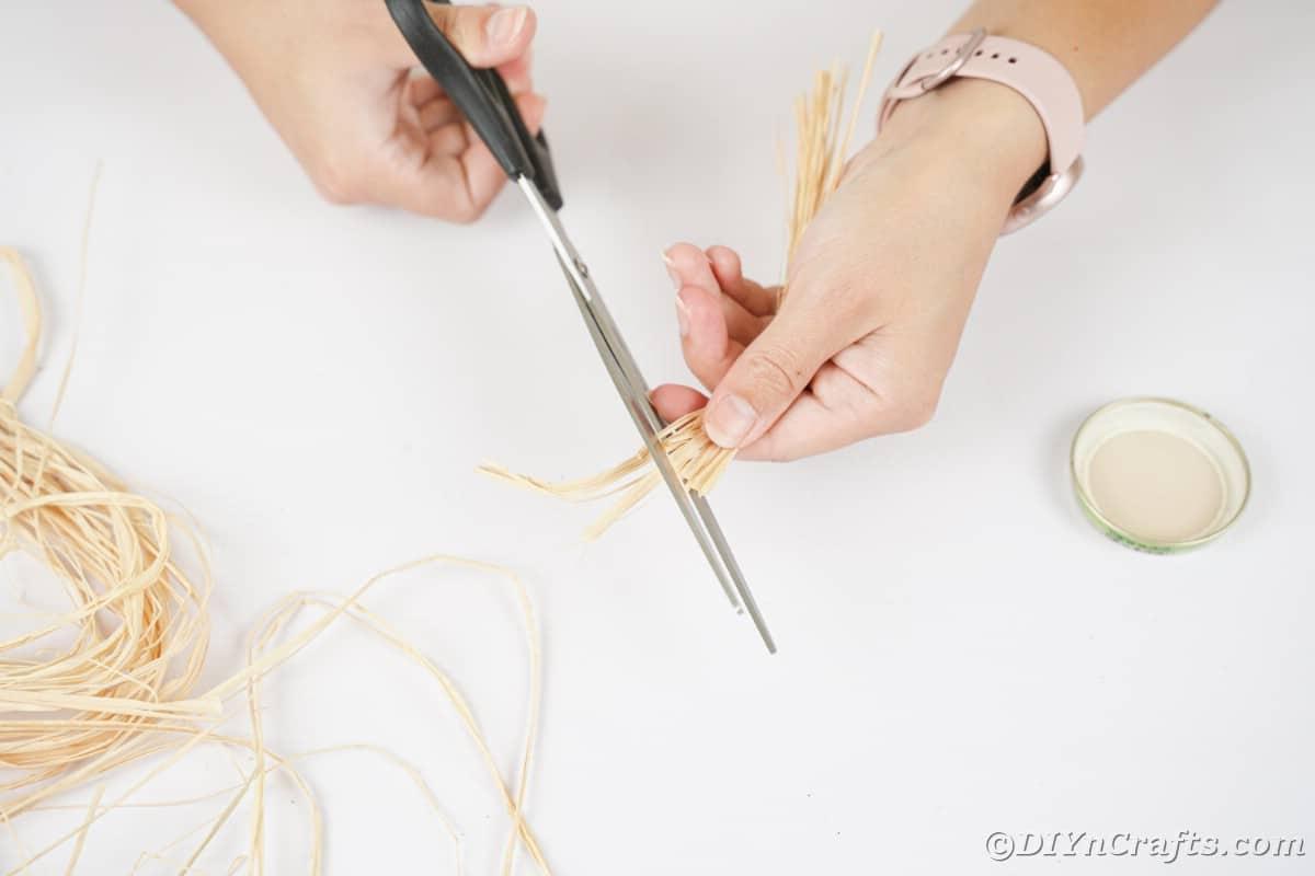 Mão segurando uma tesoura preta cortando ráfia