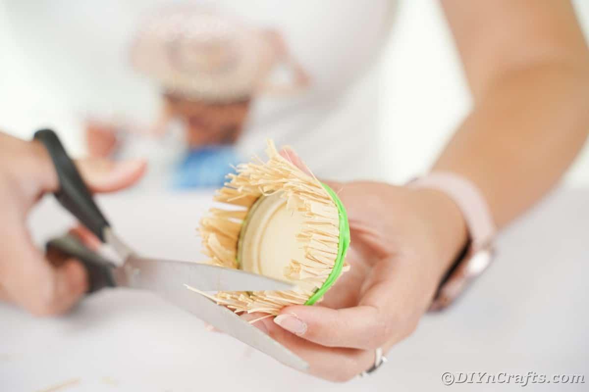 Mão segurando a tampa com bordas aparadas de ráfia com tesoura