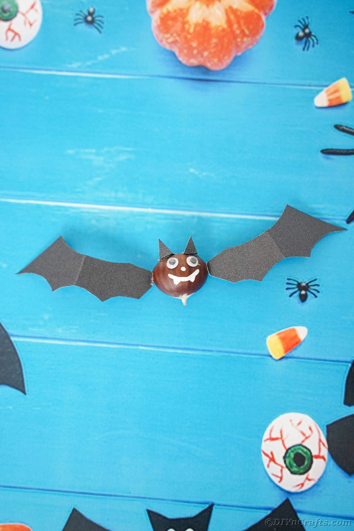 Black bat craft laying on blue paper with fake pumpkins